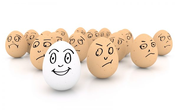 One happy smiling egg amongst sad angry and envious crowd of eggs isolated on white background